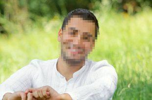 בחור יושב על הדשא עם פנים מטושטשות