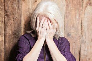 אישה מבוגרת מכסה את הפנים